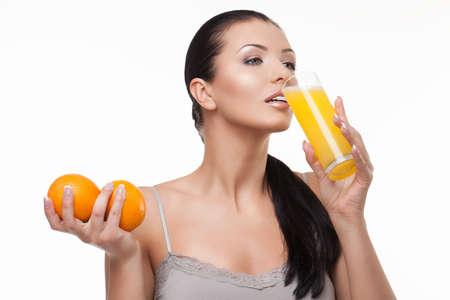 Beautiful brunette drinking orange juice from glass and holding two oranges photo