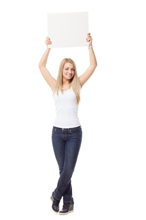 Standing young blond girl in white top and jeans holding big card over her head photo