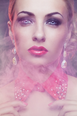 Close-up portrait of gorgeous woman in fog with bright make-up wearing red collar covered with crystals photo