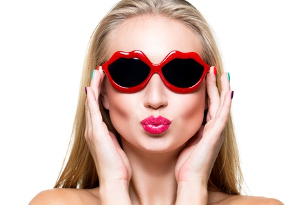 Close-up portrait of beautiful young girl with red lips wearing lips-shaped sunglasses photo