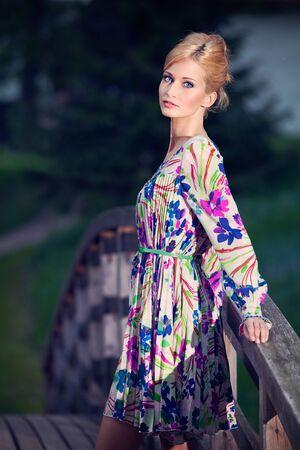 Portrait of beautiful young girl on wooden bridge outside photo