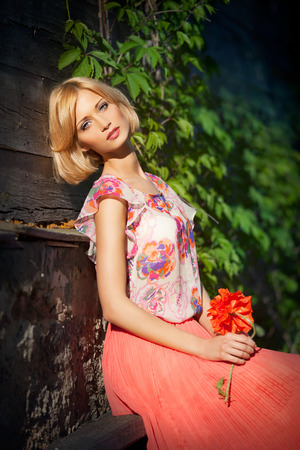 Young beautiful blond girl in long coral skirt with poppy sitting on bench photo