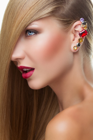 Portrait of beautiful girl with bright makeup and big earring with colorful crystals photo