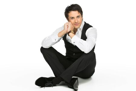 man in suite: Portrait of handsome brunette young man dressed in suit sitting on the floor over white background