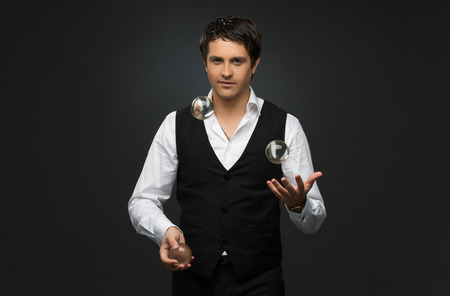 Handsome young man dressed in suit juggling three glass balls over black background Standard-Bild