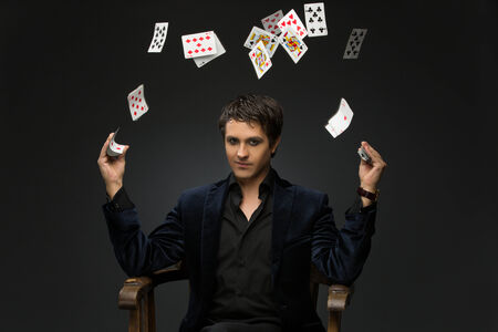 Handsome young man dressed in black suit juggling playing cards over black background