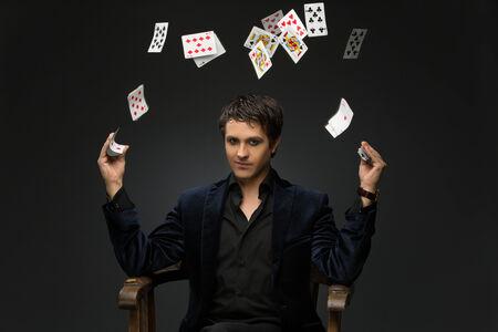 Knappe jonge man, gekleed in zwart pak jongleren met speelkaarten op een zwarte achtergrond