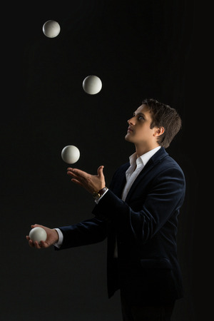 Handsome young man dressed in suit juggling white balls over black background