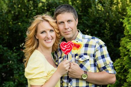 Beautiful couple holding heart shaped red and yellow lollipops photo