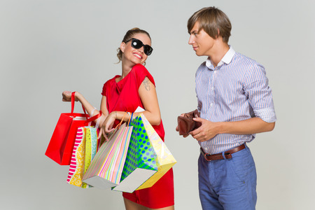 Young man with empty wallet and beautiful girl with many shopping bags