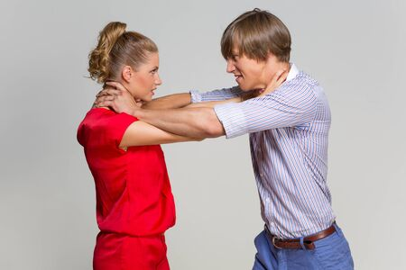 strangling: Young couple strangling each other over grey background