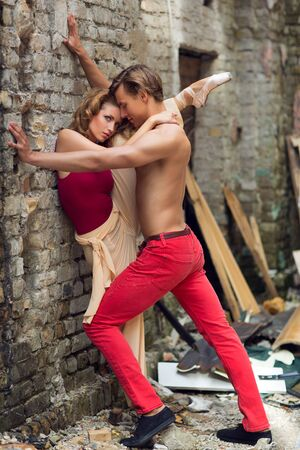 trashed: Dancer holding ballerina with her leg up against brick wall in trashed street