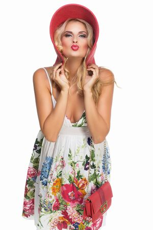 Beautiful blond girl wearing white dress with flower print, big red summer hat and little purse photo