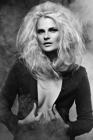 Portrait of beautiful blond girl with big hair and bright makeup wearing black jacket over naked body photo