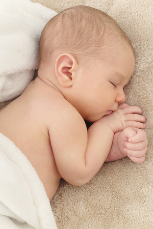 Portrait of sleeping newborn baby on beige cover Stock Photo