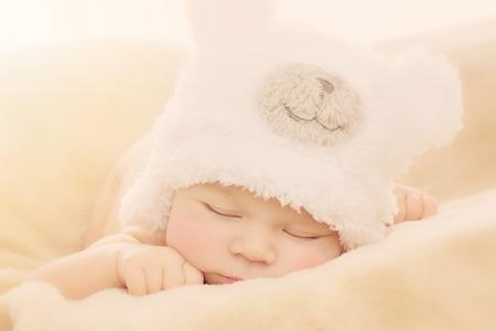 Portrait of newborn baby boy wearing funny bear shape hat sleeping on soft beige cover Standard-Bild