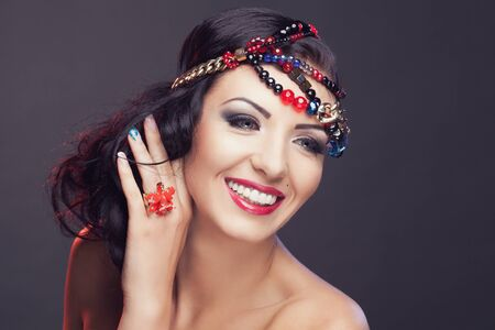 Close-up portrait of beautiful smiling brunette wearing colorful beads on her head and red lily ring photo