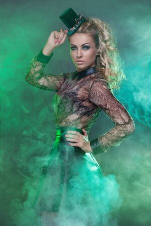 Beautiful young blond woman in green fog wearing small hat photo