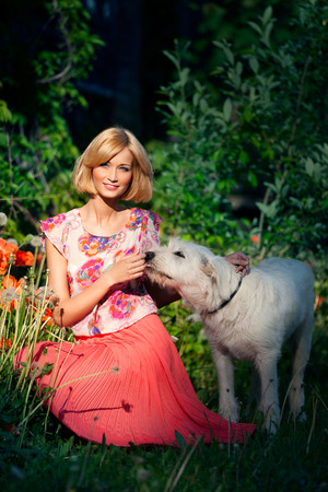 long skirt: Beautiful young blond girl in coral long skirt with white big dog