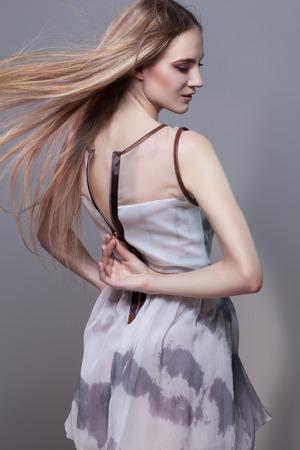 Beautiful girl opening back zipper on her short dress