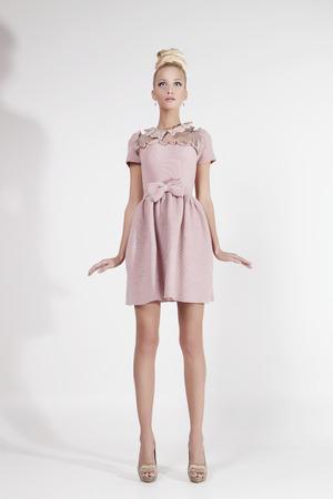 Beautiful blond girl in pink dress looking like Barbie doll photo