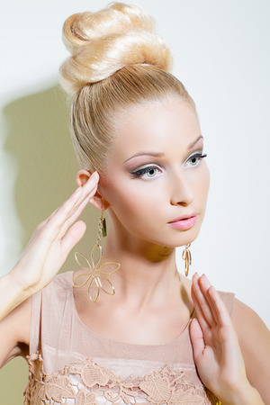 Portrait of beautiful blond girl looking like doll