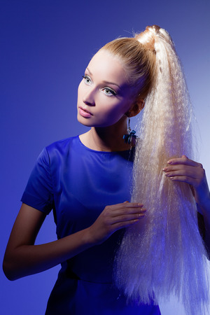 Portrait of beautiful blond girl in long blue dress looking like doll over blue background photo