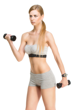 Sporty young girl exercising with dumbbells over white  photo
