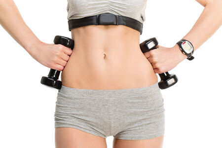 Sporty girl holding black dumbbells near her flat tummy over white  photo