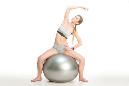 Sporty young girl exercising on a ball over white  photo