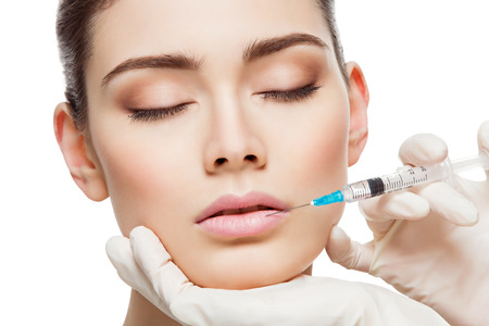 Closeup of beautiful woman gets injection in her lips. Isolated over white background Foto de archivo