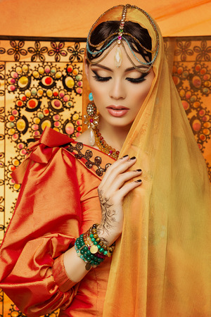 Beautiful young bride wearing orange dress and long veil sniffing with bright makeup