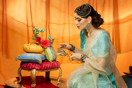 slice of cake: Beautiful young woman dressed in oriental style taking piece of wedding cake Stock Photo