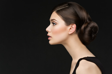 Closeup shot of beautiful young woman profile over black background Imagens