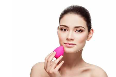 foundations: Beautiful young woman applying makeup using beauty blender sponge. Isolated over white background