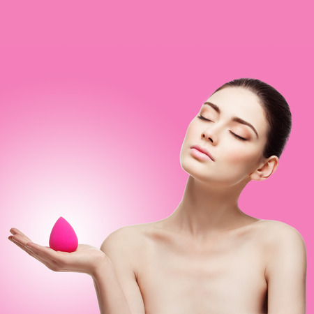 Beautiful young woman holding beauty blender sponge. Square composition. Isolated over pink background with gradient Stock Photo