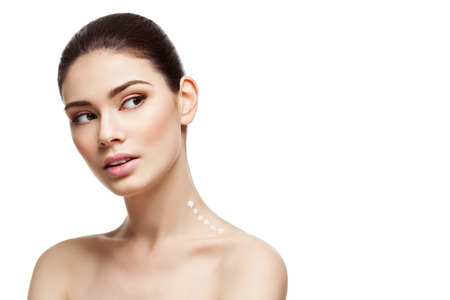 Beautiful young woman with moisturizing cream drops on neck. Beauty image. Copy space. Isolated over white background