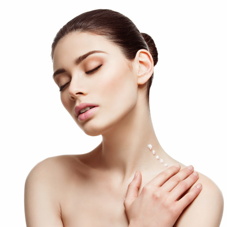 Beautiful young woman applying moisturizing cream on her neck. Beauty image. Square composition. Isolated over white background.