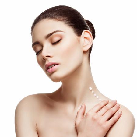 the neck: Giovane e bella donna applicare la crema idratante sul suo collo. Immagine di bellezza. Piazza composizione. Isolato su sfondo bianco.
