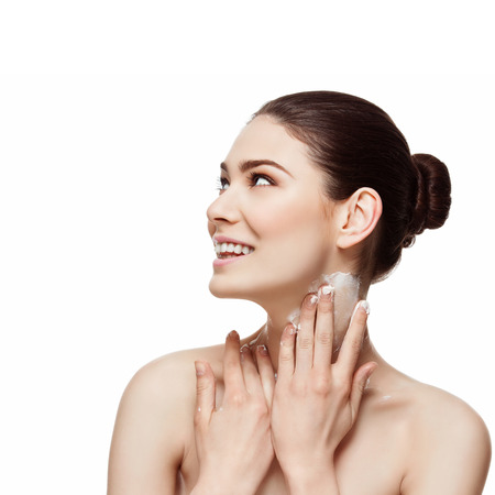 Beautiful happy young woman applying moisturizing cream on her neck. Beauty image. Copy space. Square composition. Isolated over white background. Stock Photo - 38351419