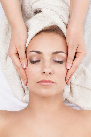 Young beautiful woman receiving face massage in spa salon