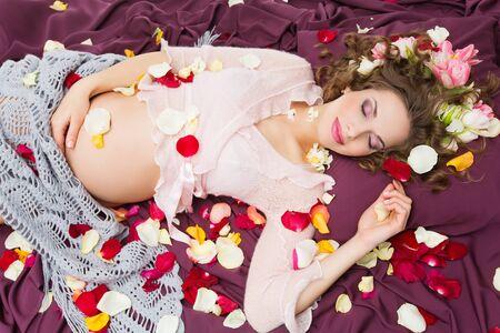 mujer con rosas: Mujer embarazada hermosa joven tendido en telas violetas vestidos de blusa y cubiertos con el mant�n