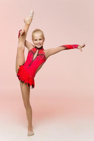 calisthenics: Studio portrait of beautiful young blonde girl gymnast training calisthenics exercise Stock Photo