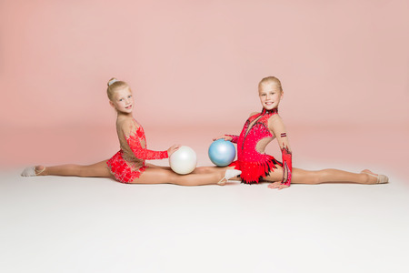 contortionist: Two smiley gymnasts posing with balls on light pink background
