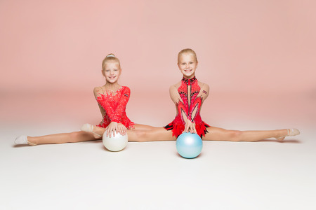 synchronously: Two gymnast in red clothes sitting in front of pink background