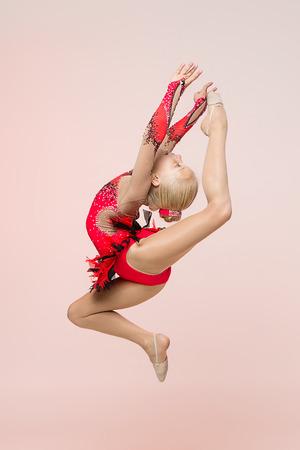 gymnastique: Jeune gymnaste de fille sautant sur fond rose p�le