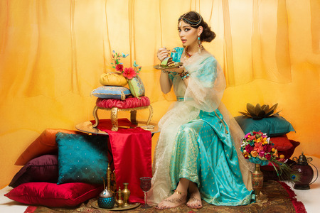 Beautiful young woman dressed in oriental style eating luxurious wedding cake