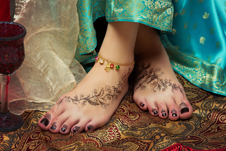 Beautiful oriental girl feet with bracelet and mendi drawing Stock Photo