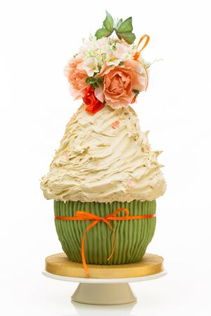 tort: Luxurous wedding tort looking like big cupcake with flower bouquet and two kissing butterflies on the top Stock Photo