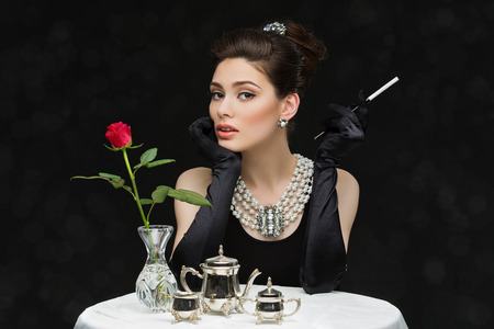 hairclip: Beautiful young girl looking like audrey hepburn sitting behind table with cegarette Stock Photo